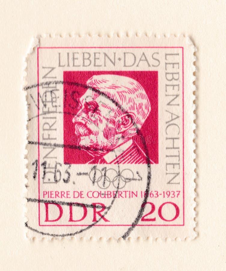 Un viejo sello germanooriental rojo con una imagen del fundador de Baron Pierre de Coubertin del comité olímpico internacional imagenes de archivo