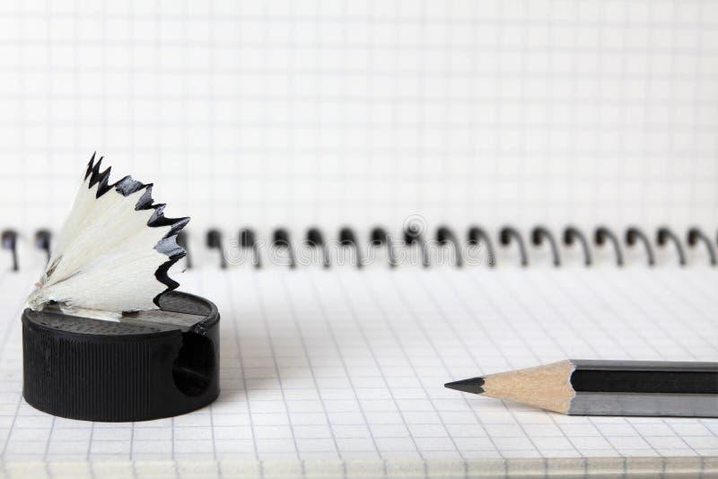 Un viejo, un de segunda mano, los sacapuntas con las virutas y un lápiz simple mienten en el cuaderno en una caja Foco selectivo  imagen de archivo