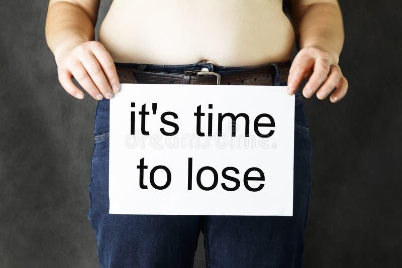 Un vientre del hombre s de la grasa sostiene una hoja del Libro Blanco limpia, o con el vapor de la inscripción para perder el pe imagen de archivo libre de regalías