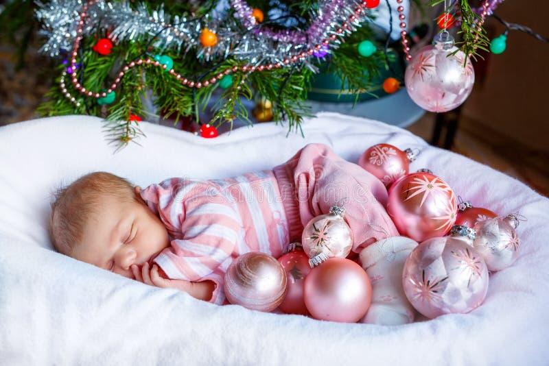 Un vieux bébé nouveau-né de semaine avec les boules roses s'approchent de l'arbre de Noël photographie stock
