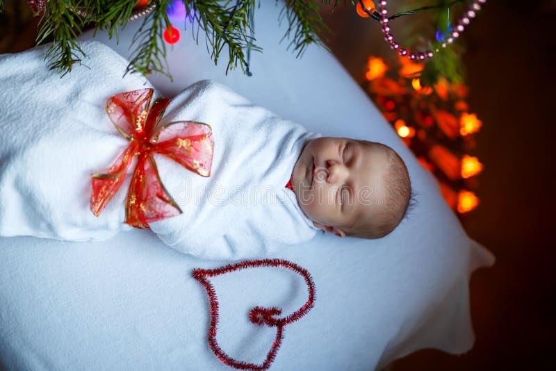 Un vieux bébé nouveau-né de semaine enveloppé dans l'arbre de Noël proche couvrant images stock