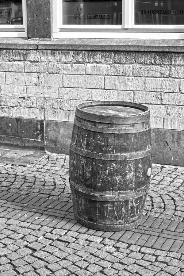 Un vieux baril sur une rue pavée en cailloutis noire et blanche photos stock