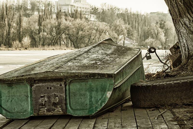 Un vieux canot de sauvetage inversé se trouve sur un quai en hiver photo stock