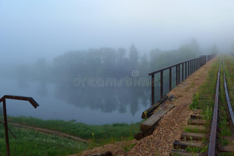 Un vieux chemin de fer fonctionnant loin à travers la rivière par la brume de matin image libre de droits