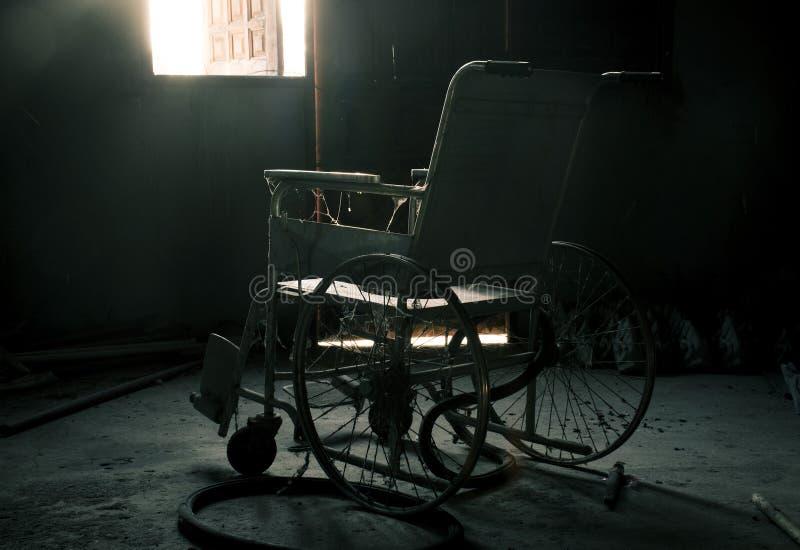 Un vieux fauteuil roulant dans la vieille chambre photo libre de droits