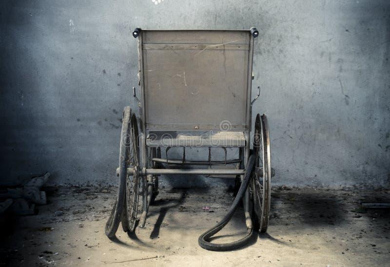 Un vieux fauteuil roulant dans la vieille chambre le vieux fauteuil roulant a été abandonné c'est concept isolé et effrayant photo stock