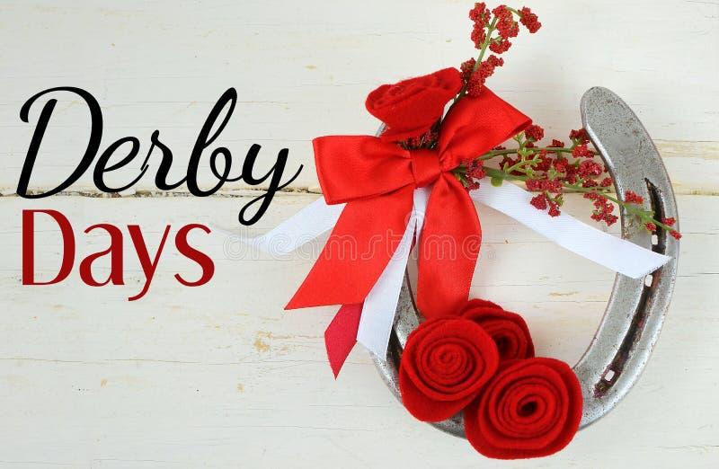 Un vieux fer à cheval décoré des roses rouges faites de feutre avec les rubans rouges et blancs sur un fond en bois rustique lavé photographie stock