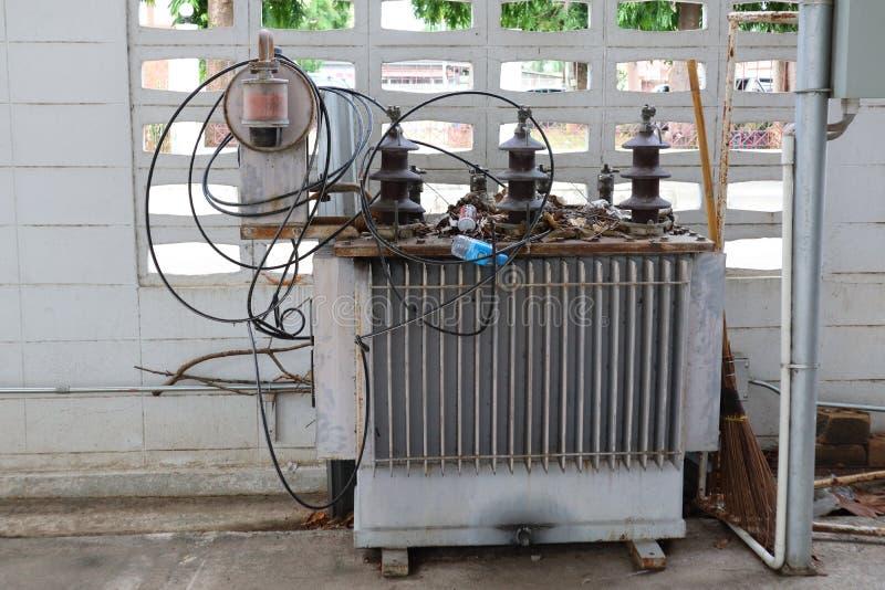Un vieux grand transformateur à l'extérieur du bâtiment pour convertir l'électricité à haute tension en électricité de basse tens photos stock