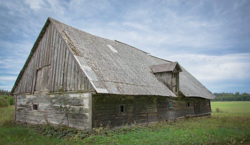 Un vieux hangar en bois abandonné avec un toit d'ardoise dans le village photos stock