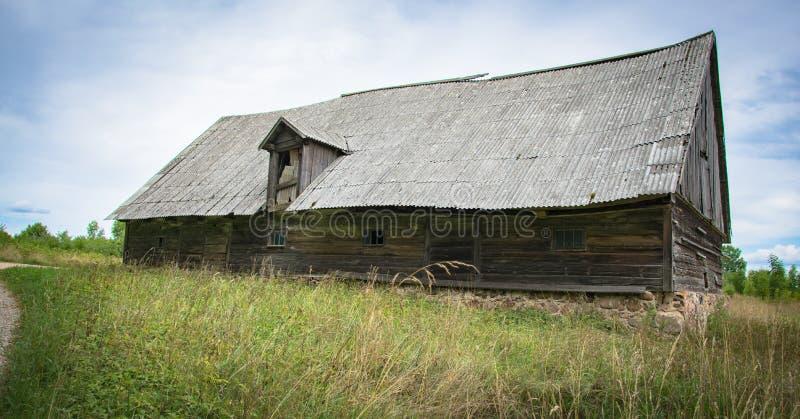 Un vieux hangar en bois abandonné avec un toit d'ardoise dans le village images libres de droits