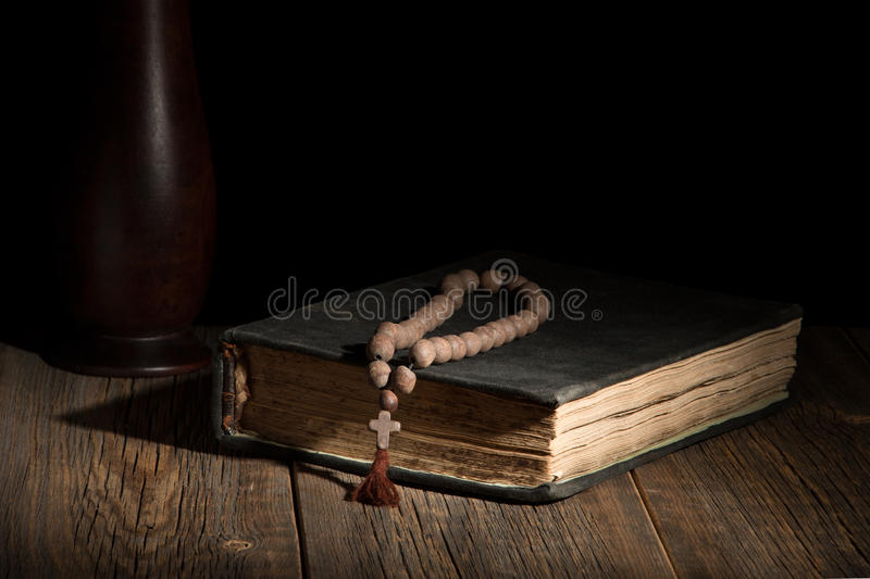 Un vieux livre sacré et un chapelet sur une table en bois photographie stock