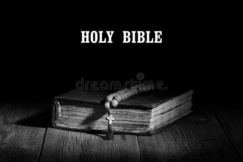 Un vieux livre sacré et un chapelet sur une table en bois images libres de droits