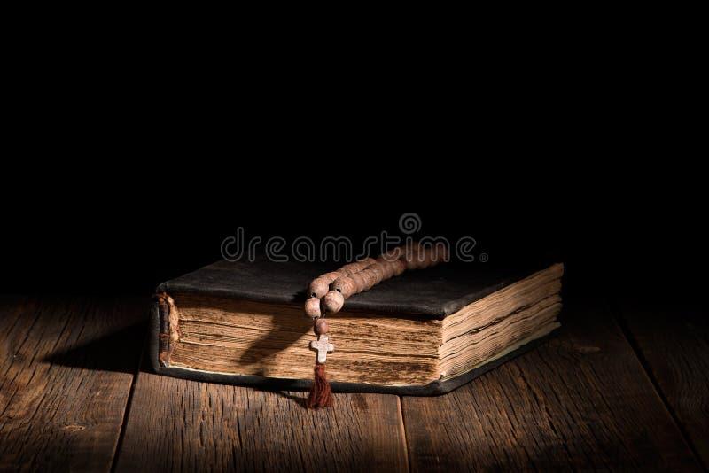 Un vieux livre sacré et un chapelet sur une table en bois photo libre de droits