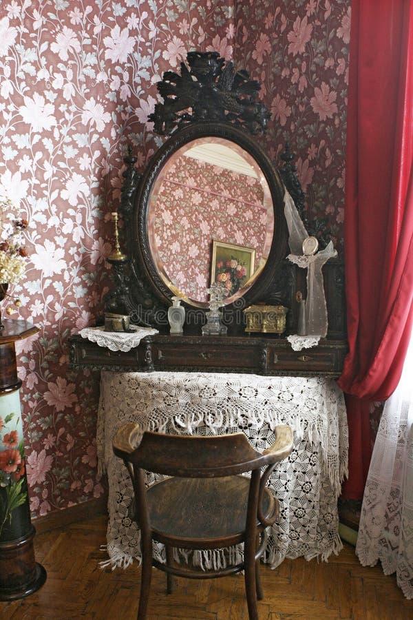 Un vieux miroir dans un cadre sur une table couverte de nappe tricotée photo stock