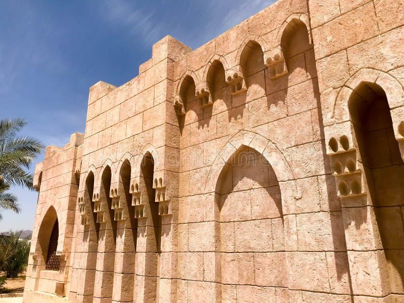 Un vieux mur fort en pierre jaune antique avec des voûtes dans les modèles et des colonnes dans un pays tropical chaud islamique  images stock