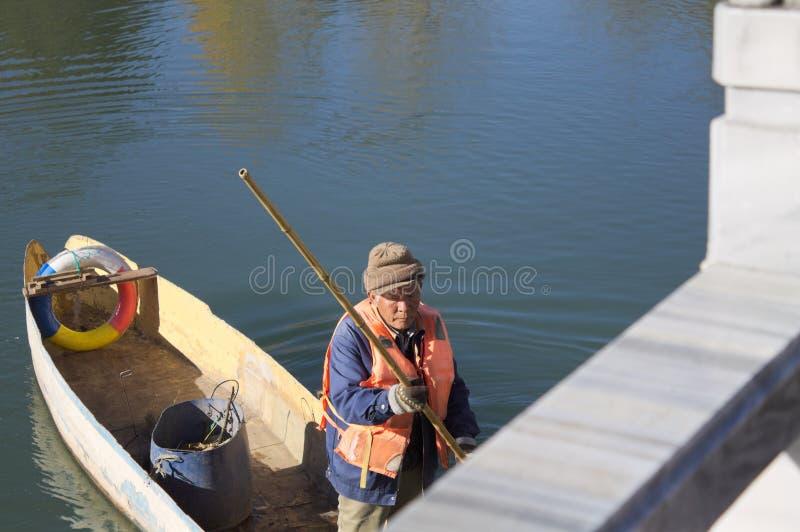 Un vieux pêcheur sur un bateau en bois dans Dragon Pool noir photographie stock libre de droits