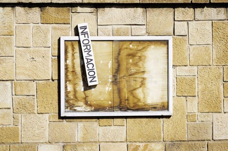Un vieux panneau d'affichage en bois abandonné accrochant sur un mur Avec un signe avec le mot espagnol pour information images stock