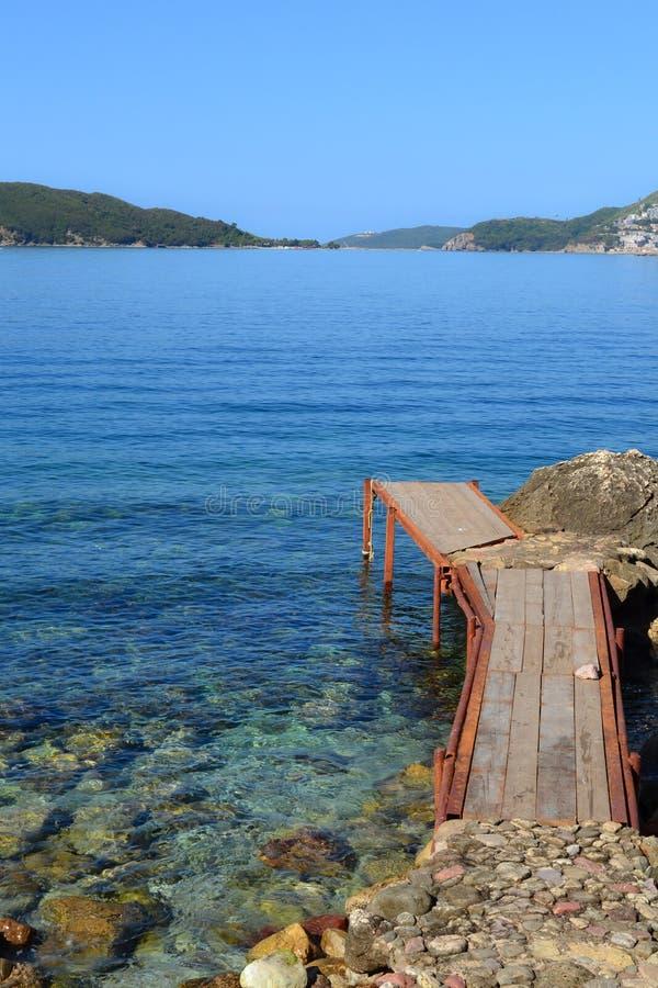 Un vieux pilier de rouillement, une jetée, un pont en mer bleue Jour ensoleillé Mer calme montenegro photos stock