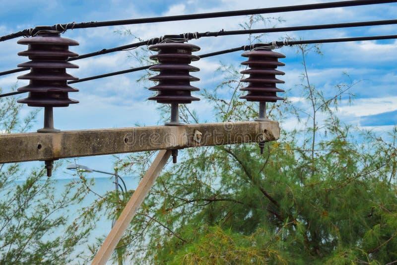 Un vieux poteau électrique avec les arbres verts autour pendant l'été avec un ciel bleu photos stock