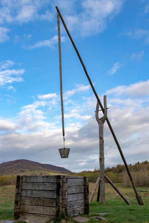 Un vieux puits dans les montagnes avec une grue Endroit de collection de l'eau dans la campagne photo libre de droits