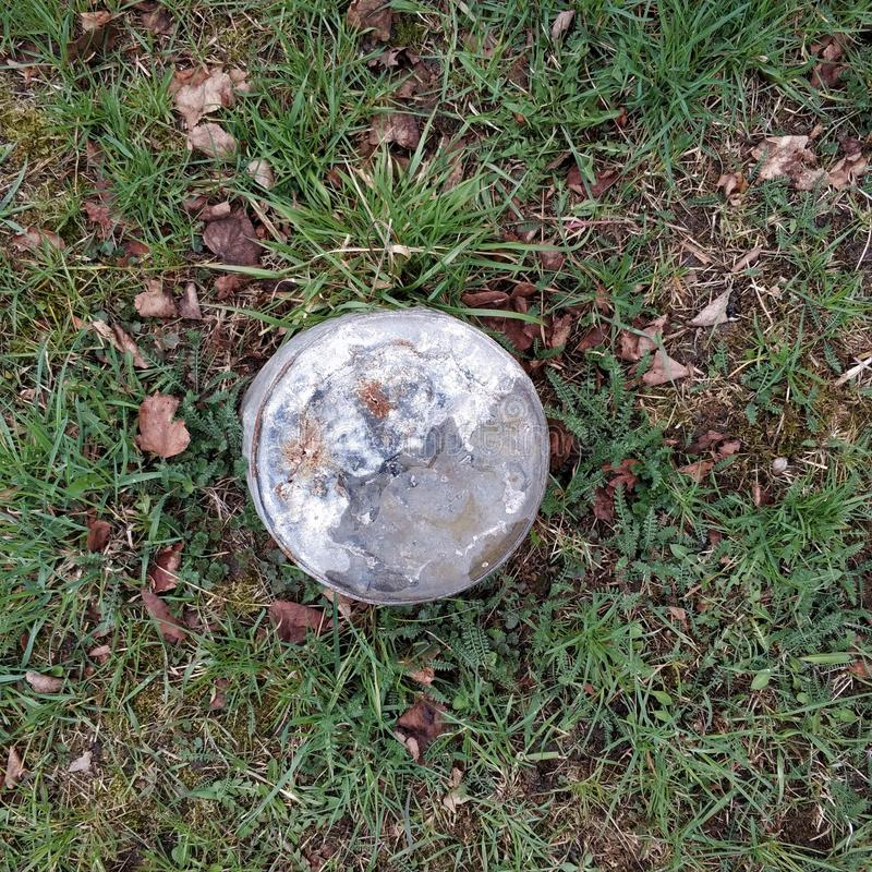 Un vieux seau rouillé est tourné à l'envers sur l'herbe photos stock