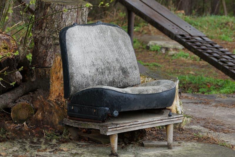 Un vieux siège de voiture gris et sale se tient dehors photo libre de droits