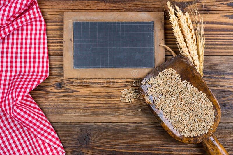 Un vieux tableau noir d'ardoise, un scoop très vieux de farine avec des grains de céréales et les oreilles de grain se trouvent s photo stock