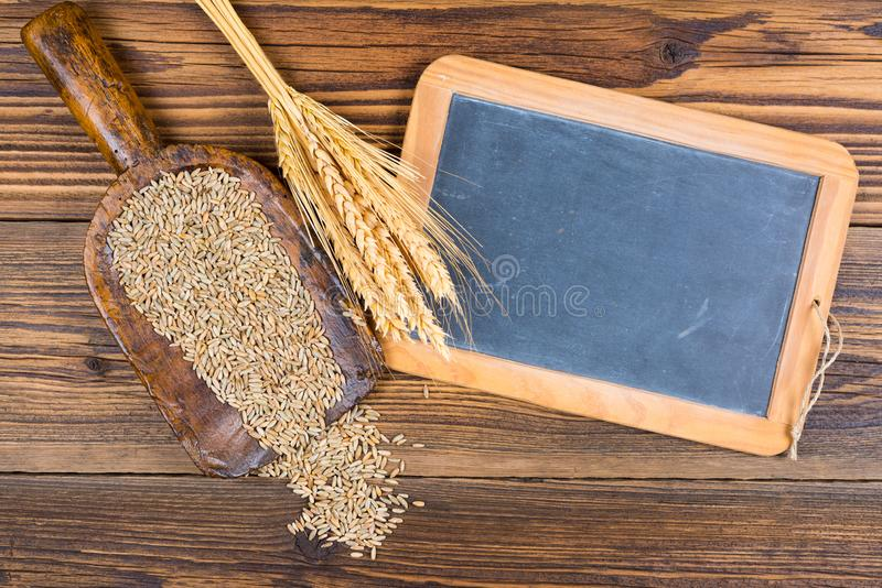 Un vieux tableau noir d'ardoise, un scoop très vieux de farine avec des grains de céréales et oreilles de grain photo stock