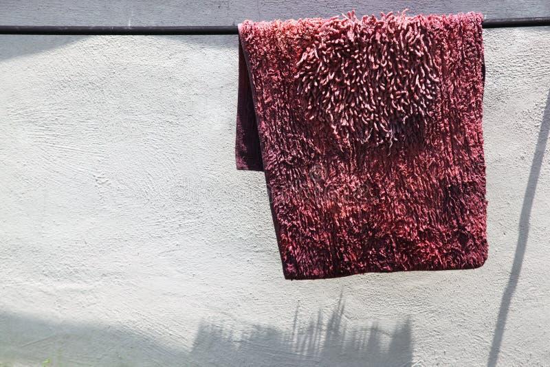 Un vieux tapis dans lavé rose et de séchage au soleil photos stock