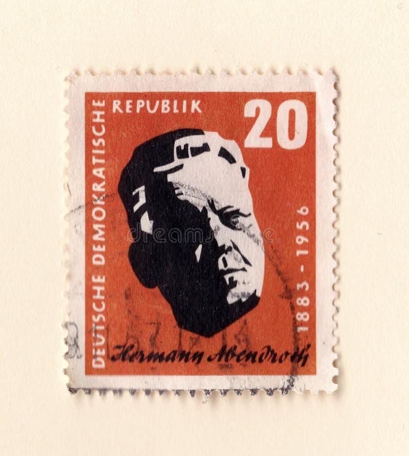 Un vieux timbre Allemand de l'Est orange avec une image de Hermann Abendroth le conducteur célèbre photographie stock libre de droits