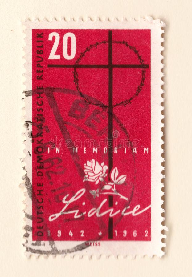 Un vieux timbre Allemand de l'Est rouge commémorant le massacre au lidice avec une rose de croix et de blanc photographie stock