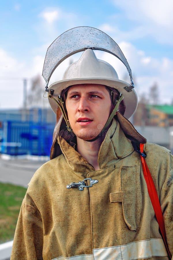 Un vigile del fuoco nel vestiario di protezione ed in un casco guarda al lato immagine stock libera da diritti