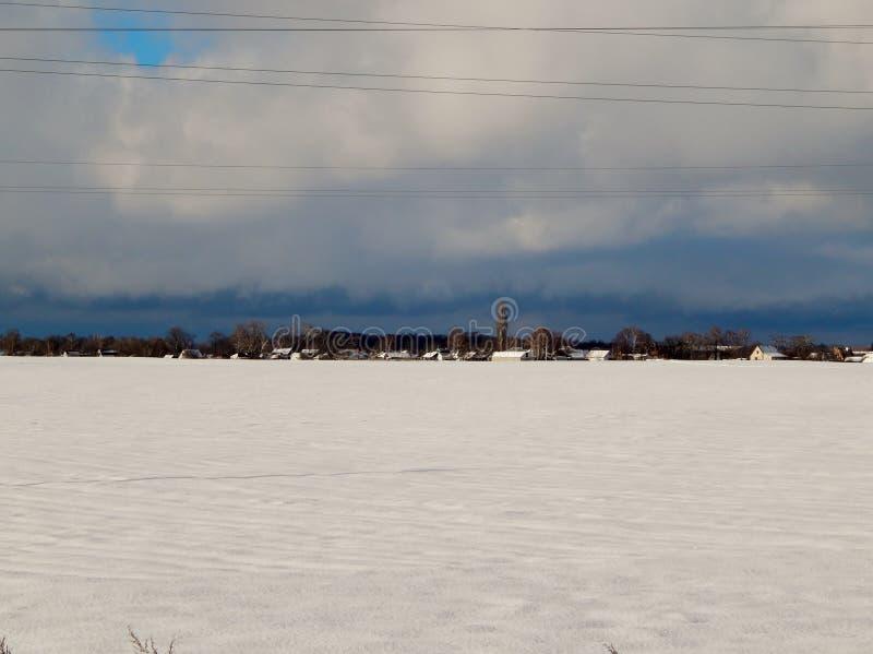 Un village descendu dans la neige et le ciel foncé photographie stock