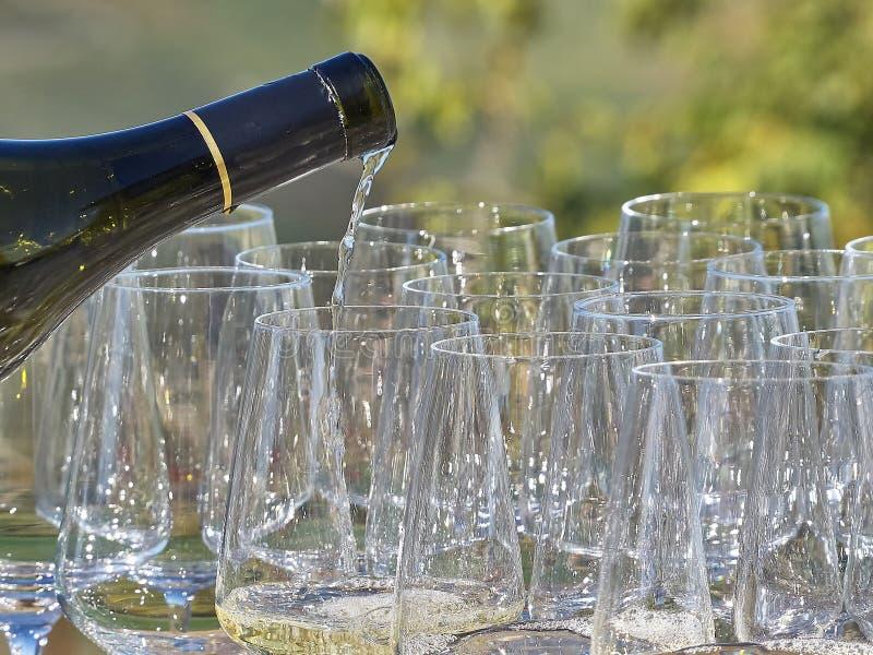 Un vin de versement de bouteille dans quelques verres avec le pays de Langhe photos stock