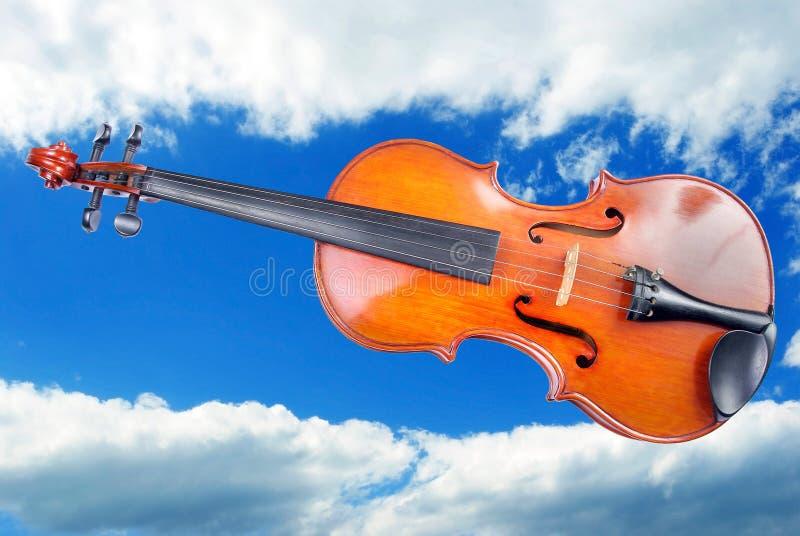 Un violín hermoso contra un cielo azul con las nubes Copie los espacios fotografía de archivo
