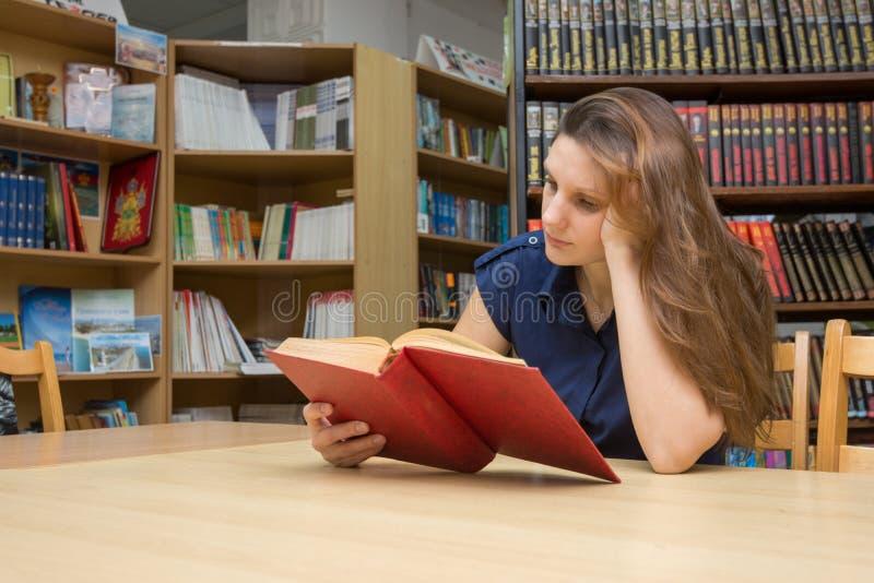 Un visitante de biblioteca lee un libro en una tabla en el cuarto de lectura fotos de archivo