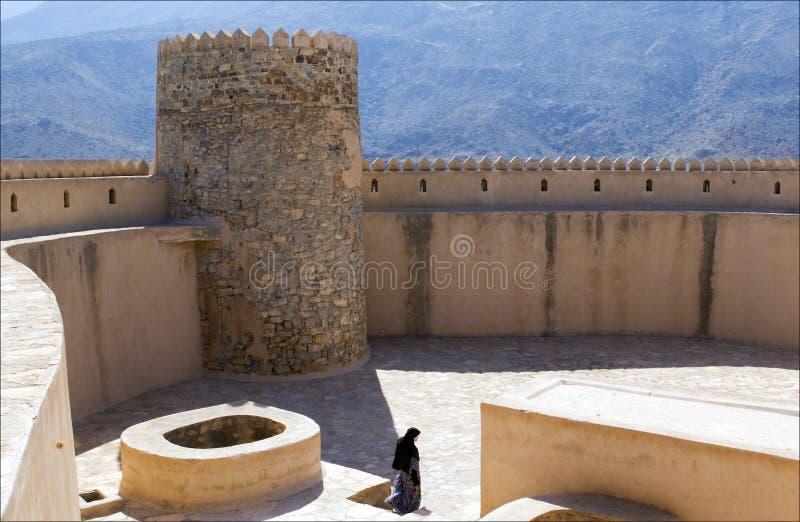 Un visitante de la señora en la tapa de la fortaleza de Rustaq, Omán imagenes de archivo