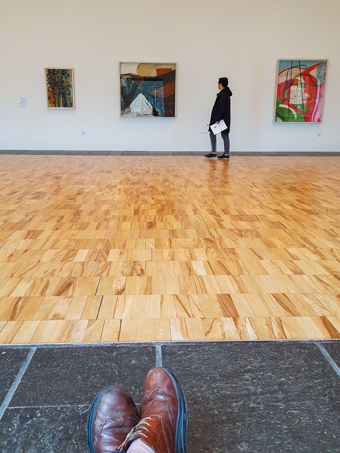 Un visiteur regarde des peintures à l'intérieur du Whitworth Art Galle photos stock