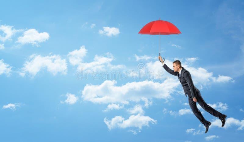 Un vol d'homme d'affaires dans le ciel et l'exploitation opacifiés un parapluie ouvert rouge photo stock