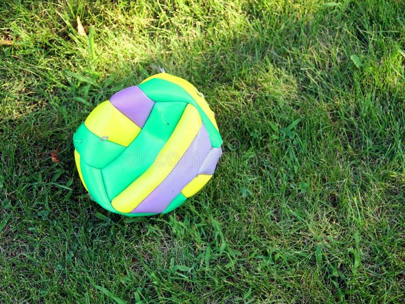 Un voleibol hinchado está mintiendo en la hierba imágenes de archivo libres de regalías
