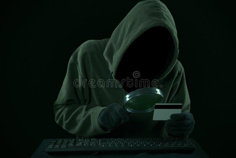 Un voleur regardant le code de carte de crédit photo stock