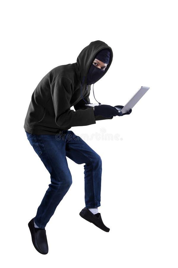 Un voleur vole un ordinateur portable image stock