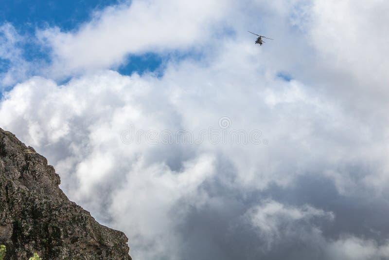 Un volo dell'elicottero di salvataggio in un cielo nuvoloso bianco Montagne e fotografie stock libere da diritti