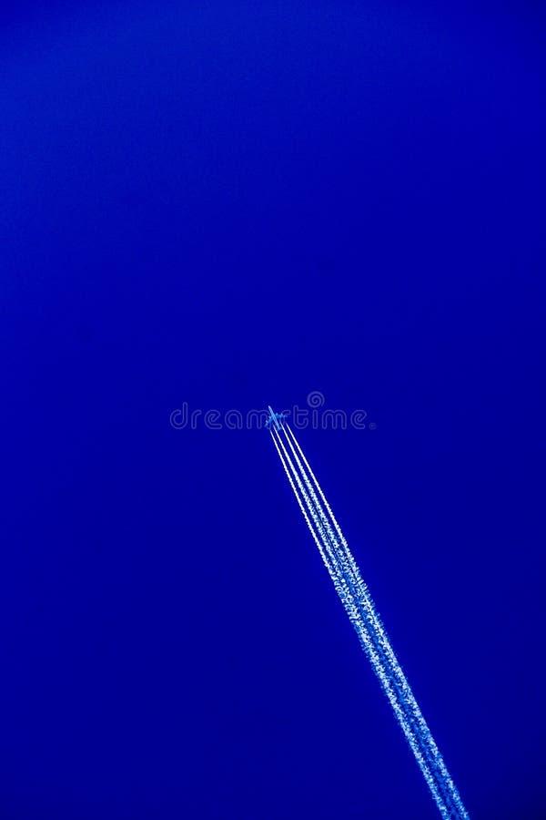Un volo piano attraverso il cielo e lasciare una traccia nei cieli immagine stock
