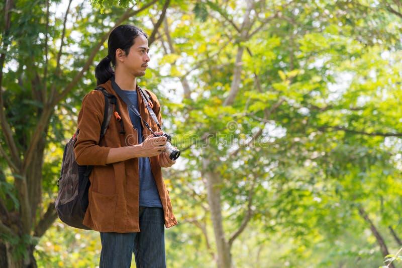 Un voyageur asiatique transportait un sac de voyage et une caméra, il se tenait dans le concept de voyage en forêt, voyage photos stock