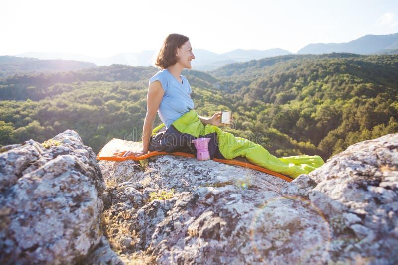 Un voyageur boit du café tout en se reposant sur une montagne image libre de droits