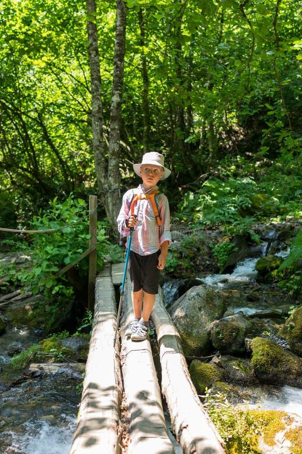 Un voyageur de garçon avec des poteaux d'un trekking se tient sur un pont délabré au-dessus d'un courant rapide image stock