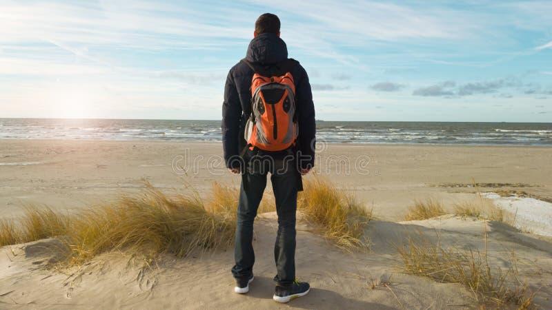 Un voyageur de jeune homme avec un sac à dos se tient sur la plage et admire la vue Penser seul à l'avenir belle lumière images stock