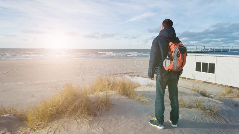 Un voyageur de jeune homme avec un sac à dos se tient sur la plage et admire la vue Penser seul à l'avenir belle lumière image libre de droits