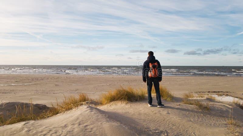 Un voyageur de jeune homme avec un sac à dos se tient sur la plage et admire la vue Penser seul à l'avenir Belle lumière, SA images libres de droits